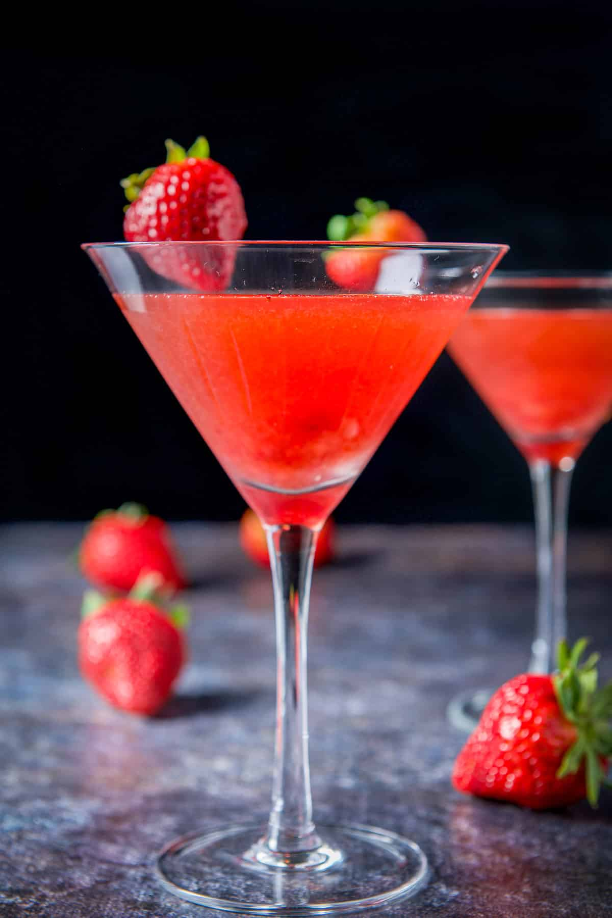Vertical view of the strawberry cosmos with strawberries on the rims as garnish and table