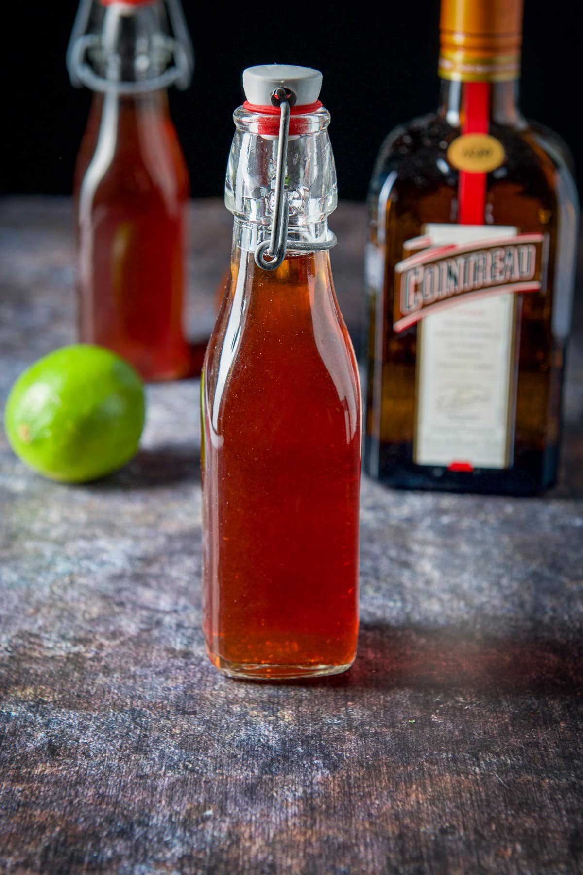 Bottle of strawberry vodka, cointreau and a lime
