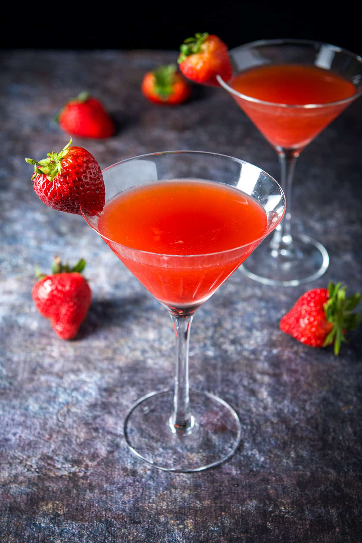 Two martini glasses filled with the strawberry cocktail with the fruit on the rims and table