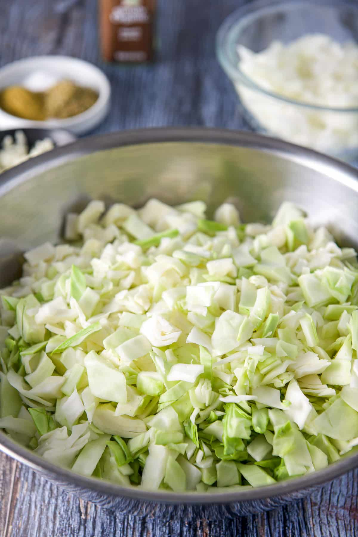 Raw cabbage chopped in a bowl, onions in a bowl and herbs in the back