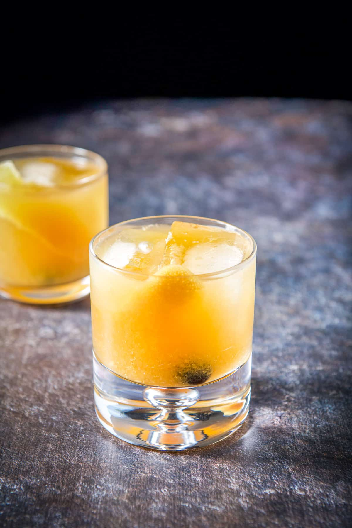 A thick glass in front of a double old fashioned glass filled with the amaretto cocktail