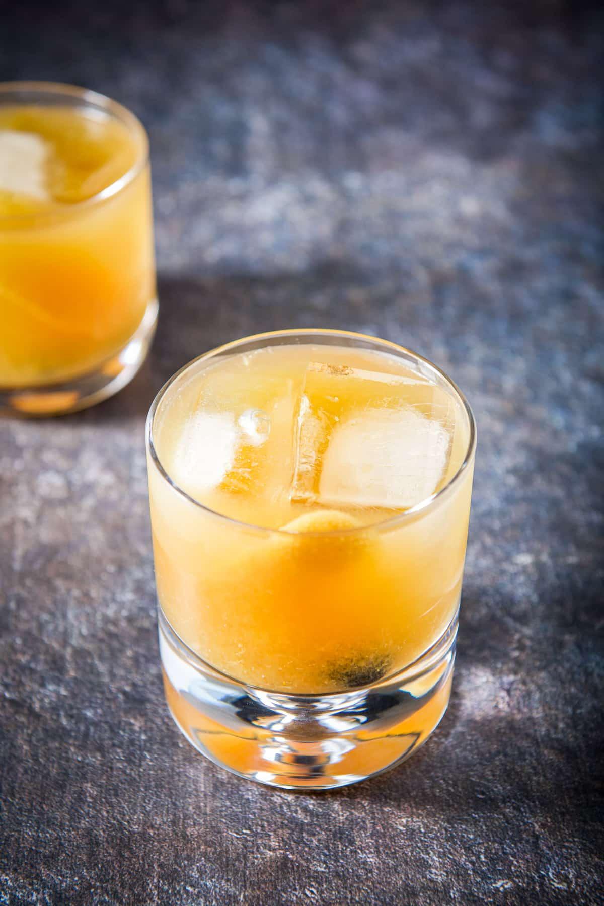 Big ice cubes in the amaretto drink with orange zest garnish