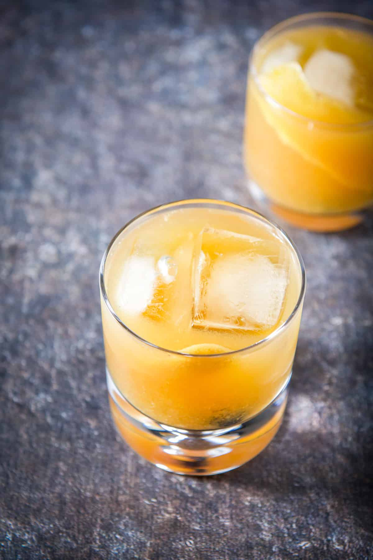 An almost overhead view of the orange juice amaretto cocktail with another in the back