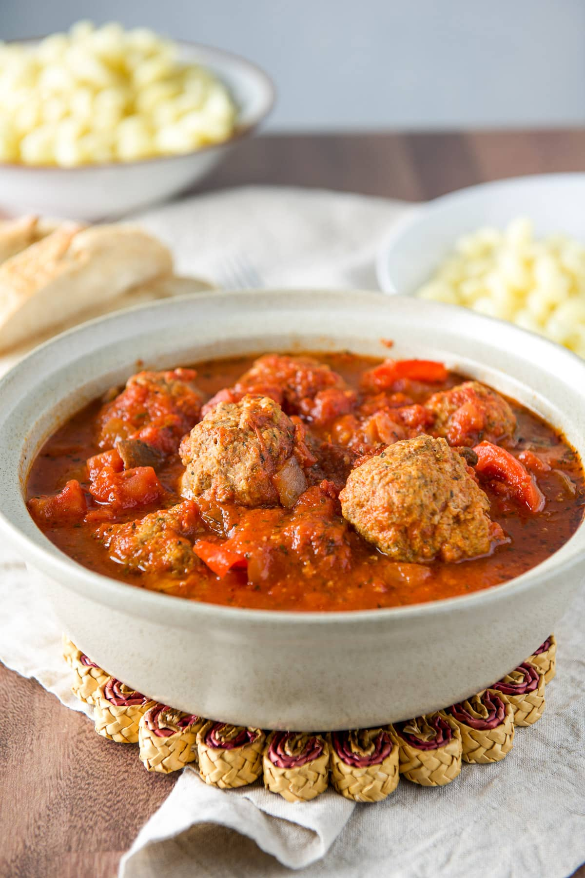 A grey bowl with sauce and meatballs with pasta and bread behind