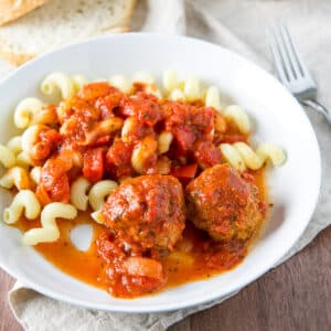 White deep dish with two meatballs, sauce and pasta - square