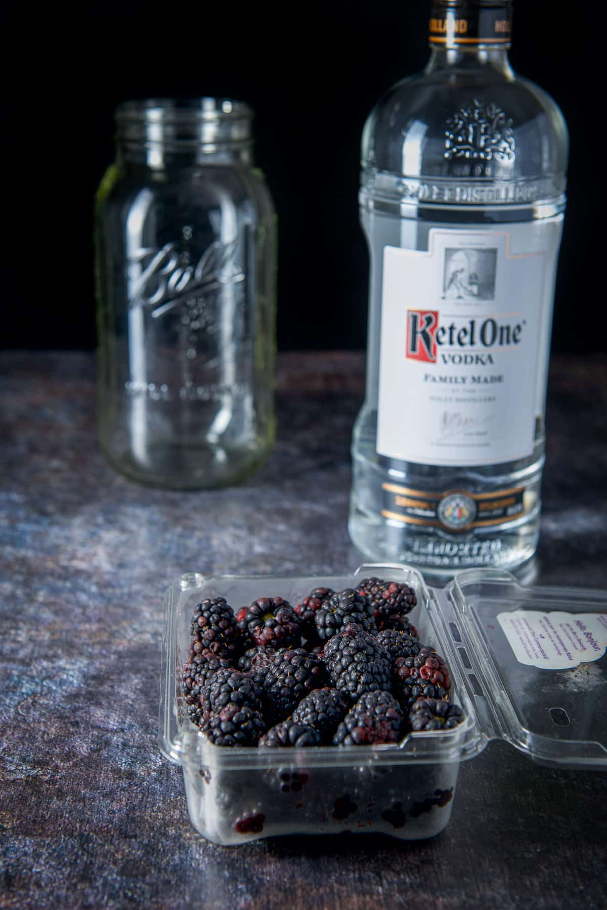 A plastic container of blackberries, bottle of vodka and a jar