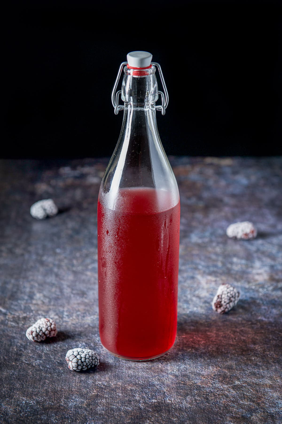 A table with frozen blackberries on it with a bottle of blackberry vodka
