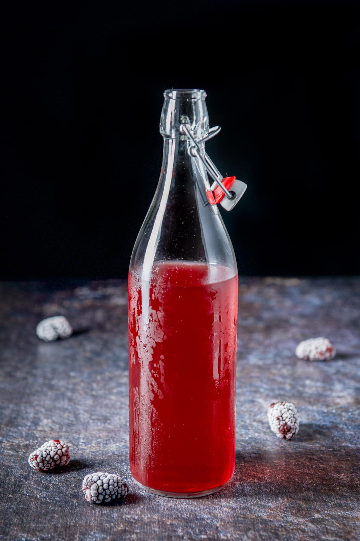 A frosty bottle with red infused vodka with 5 blackberries on a table