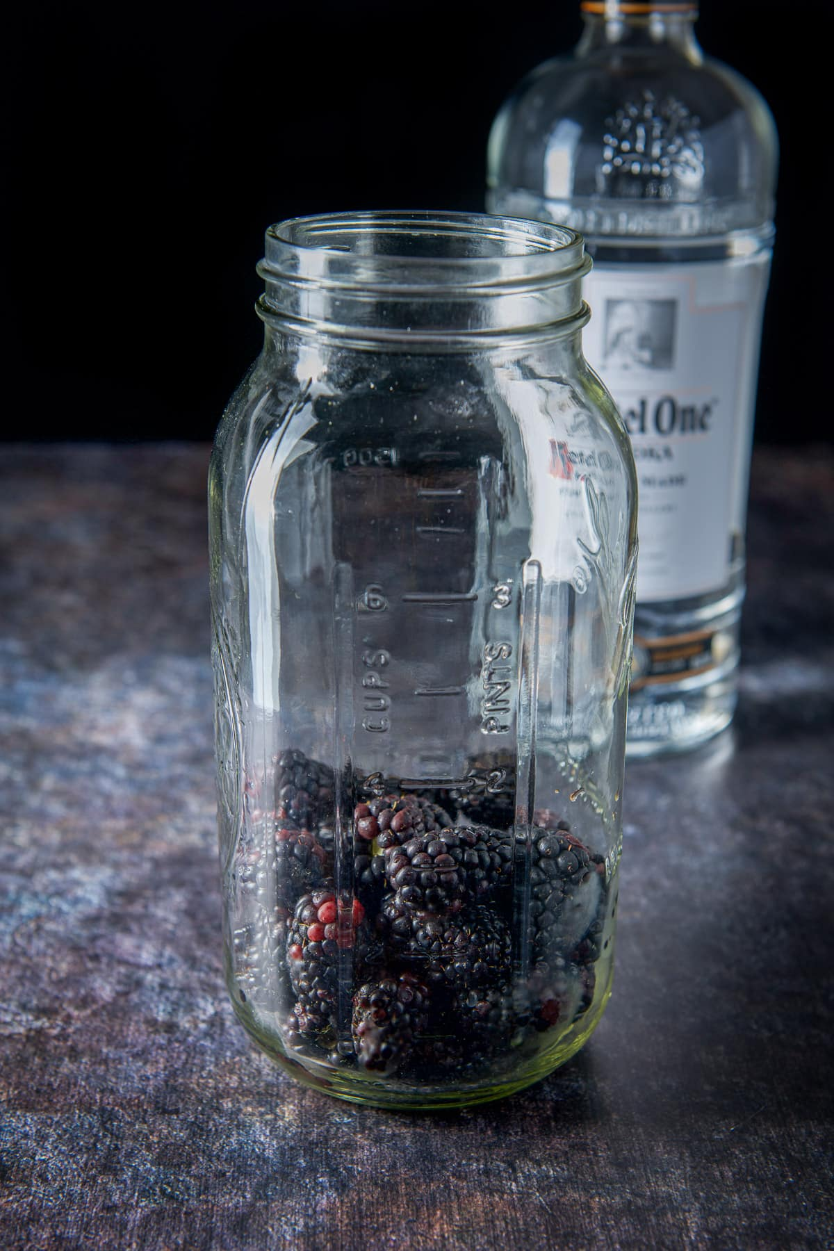 blackberries in a large jar with a bottle of vodka in the background