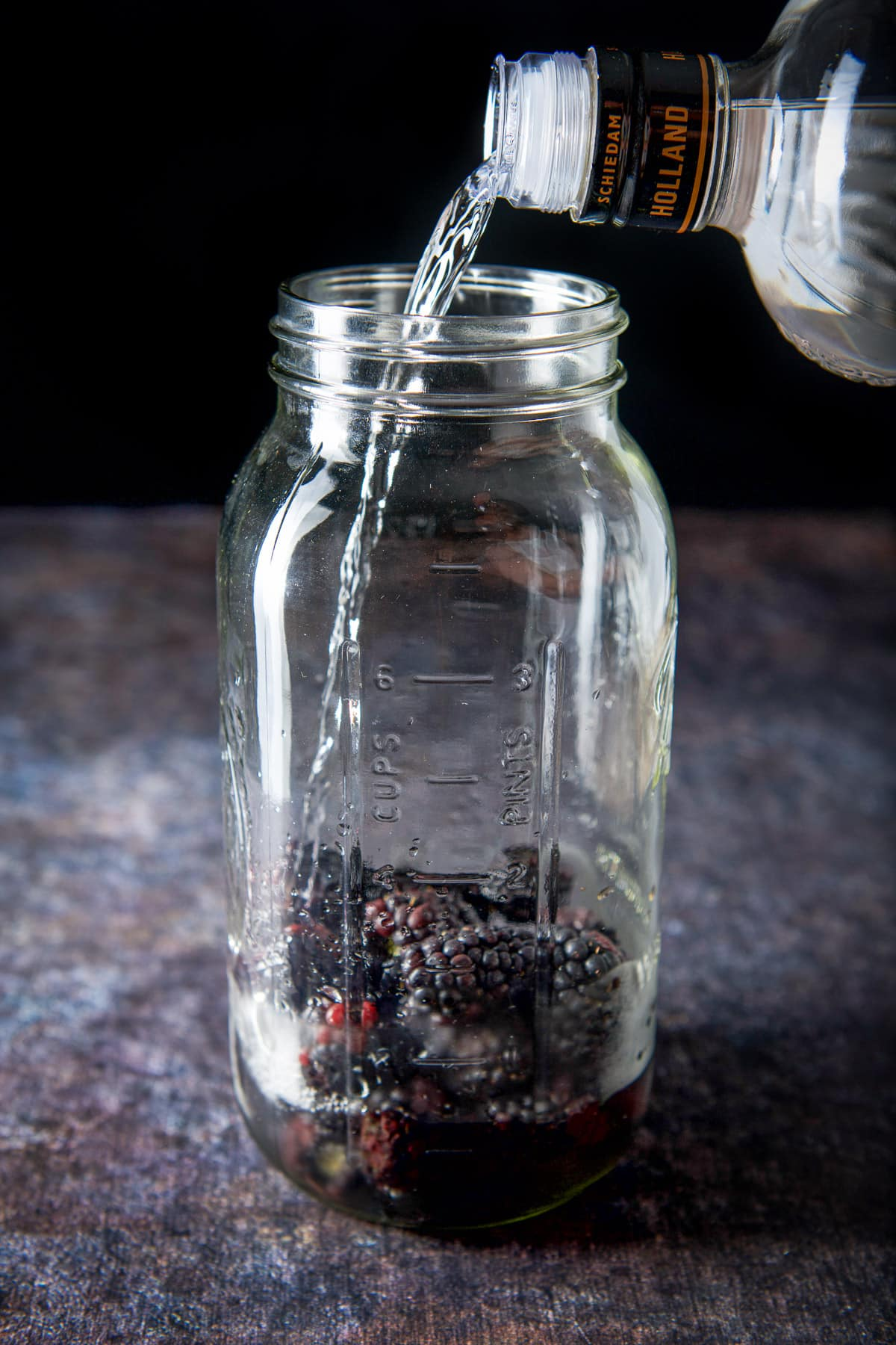 Vodka being poured into the jar of blackberries