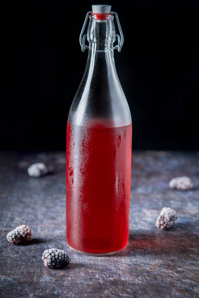 A bottle with the red vodka in it with blackberries on the table