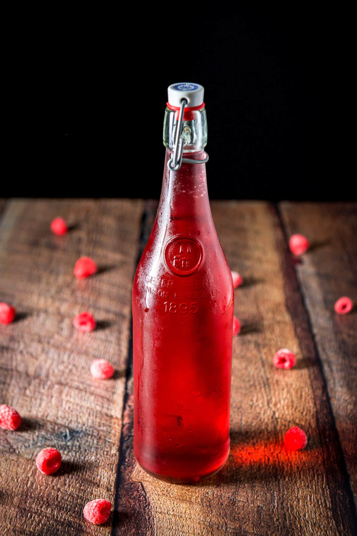 Raspberries on a table with the bottle of red vodka