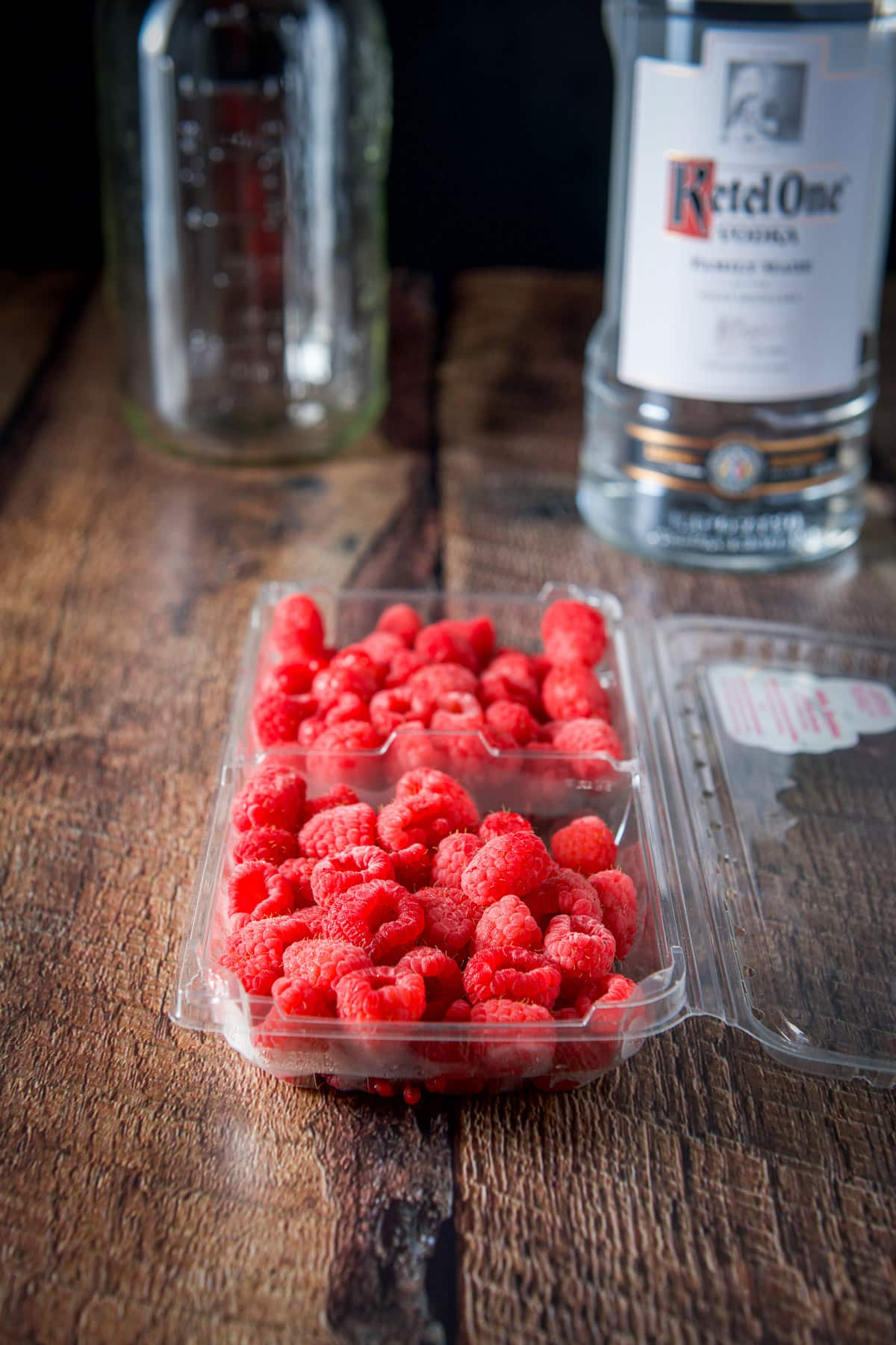Raspberries in a plastic container, a vodka bottle and jar in the background
