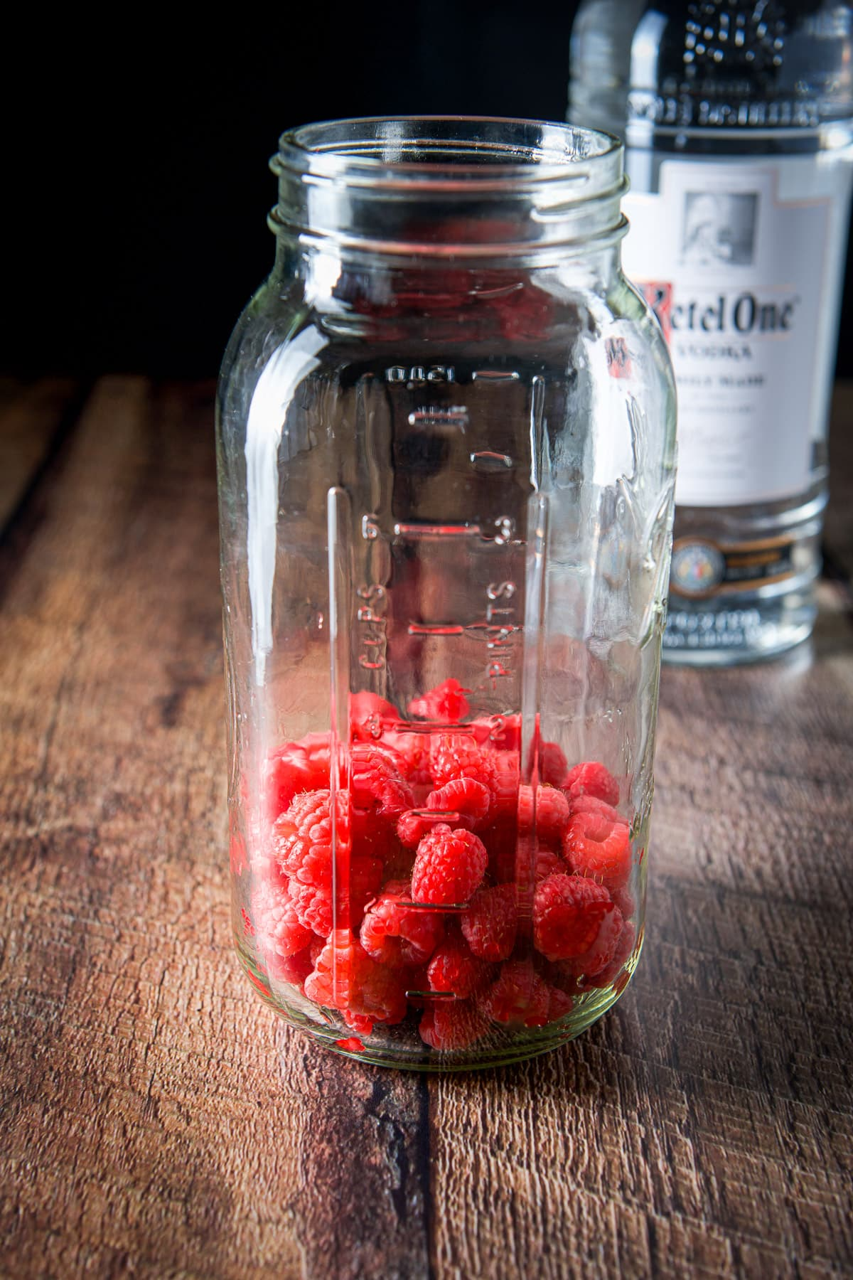 Raspberries in a large jar with the vodka in the back