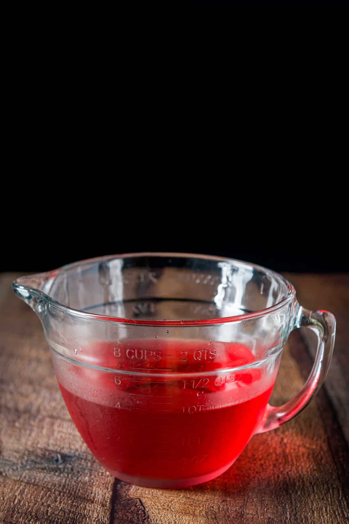 A big glass bowl with the raspberry vodka in it