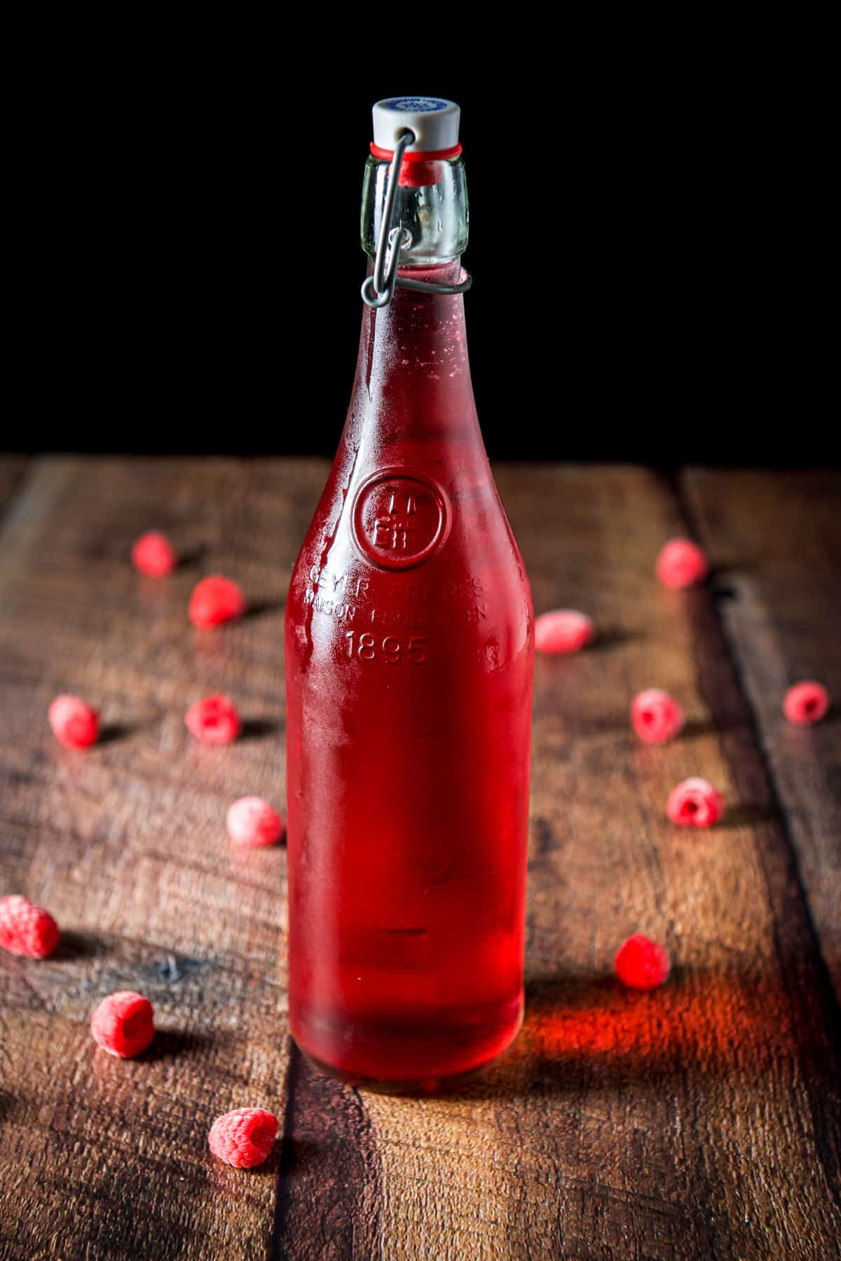 A capped bottle of red vodka with raspberries on the table