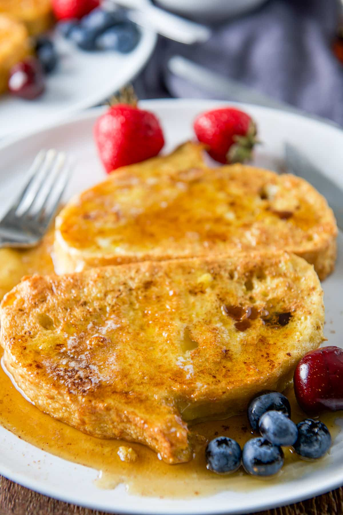 Close up of two pieces of French toast smothered with maple syrup on a plate with fruit