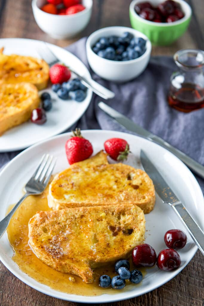 A high view of fruit on plates with French toast that has maple syrup on it
