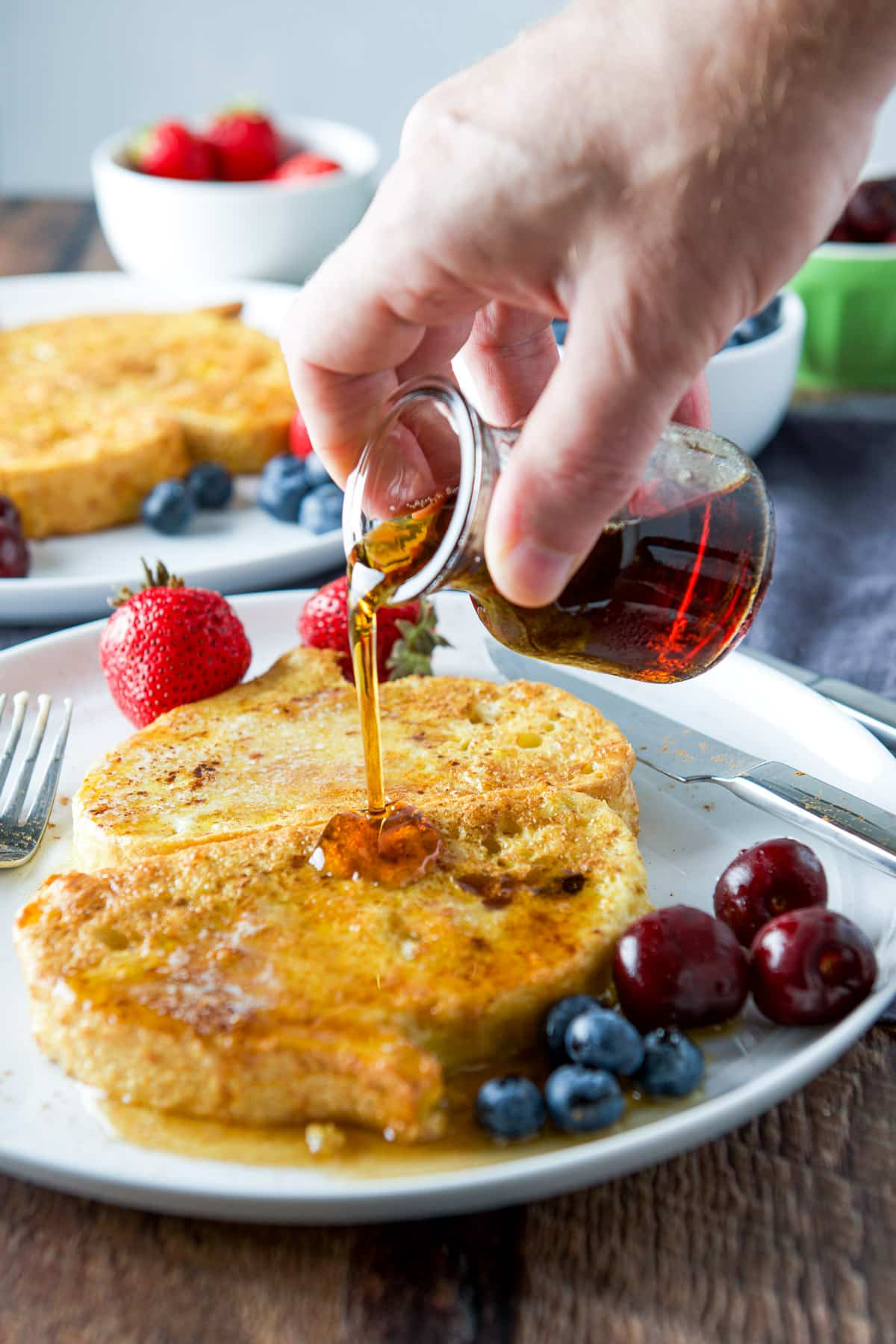 A male hand pouring maple syrup on the buttered French toast
