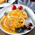 French toast smothered with maple syrup on a white plate with cherries, strawberries and blueberries