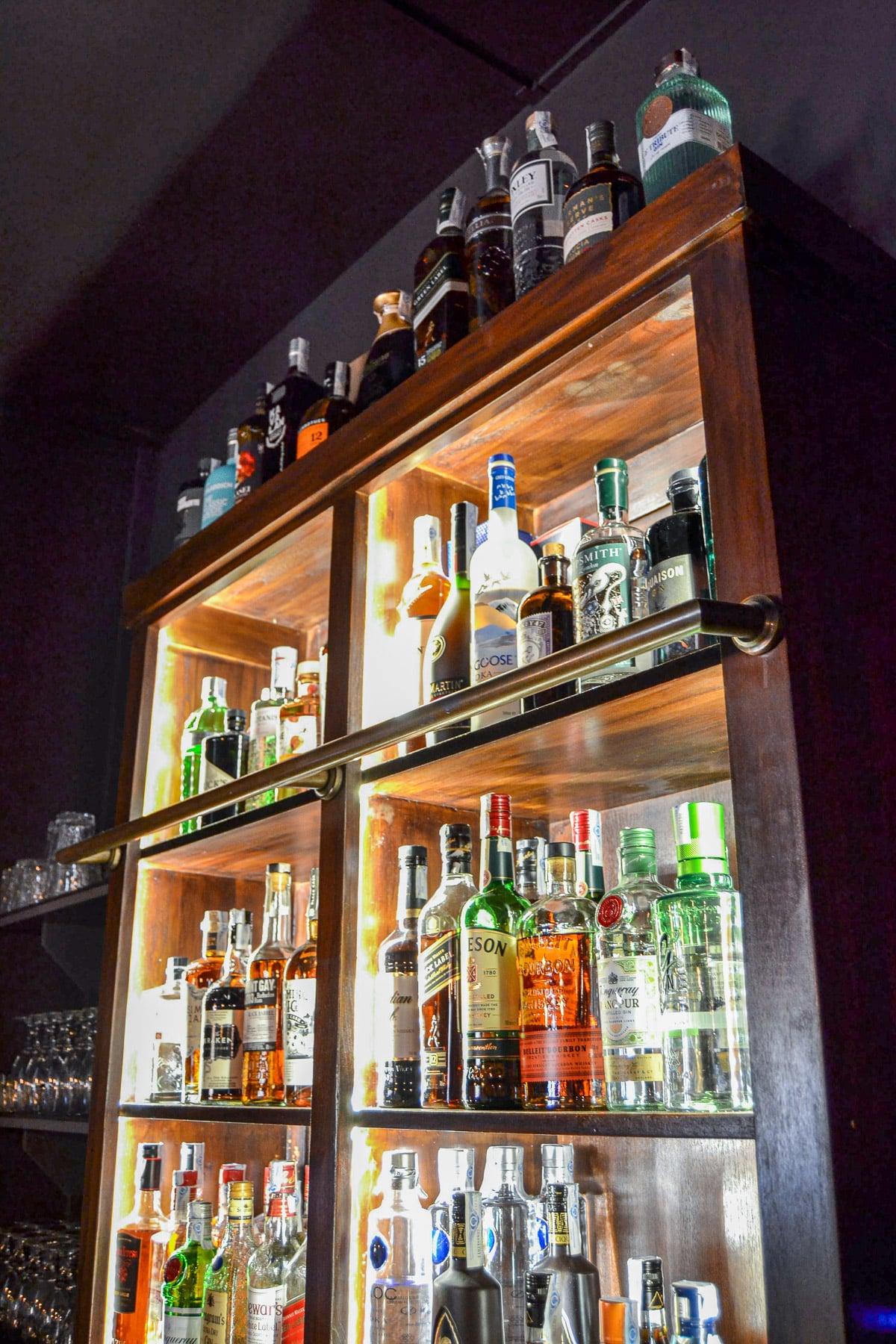 Bar photo showing lots of bottles of alcohol on wooden cabinet