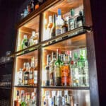 Wooden cabinet with bottles of alcohol on them - square