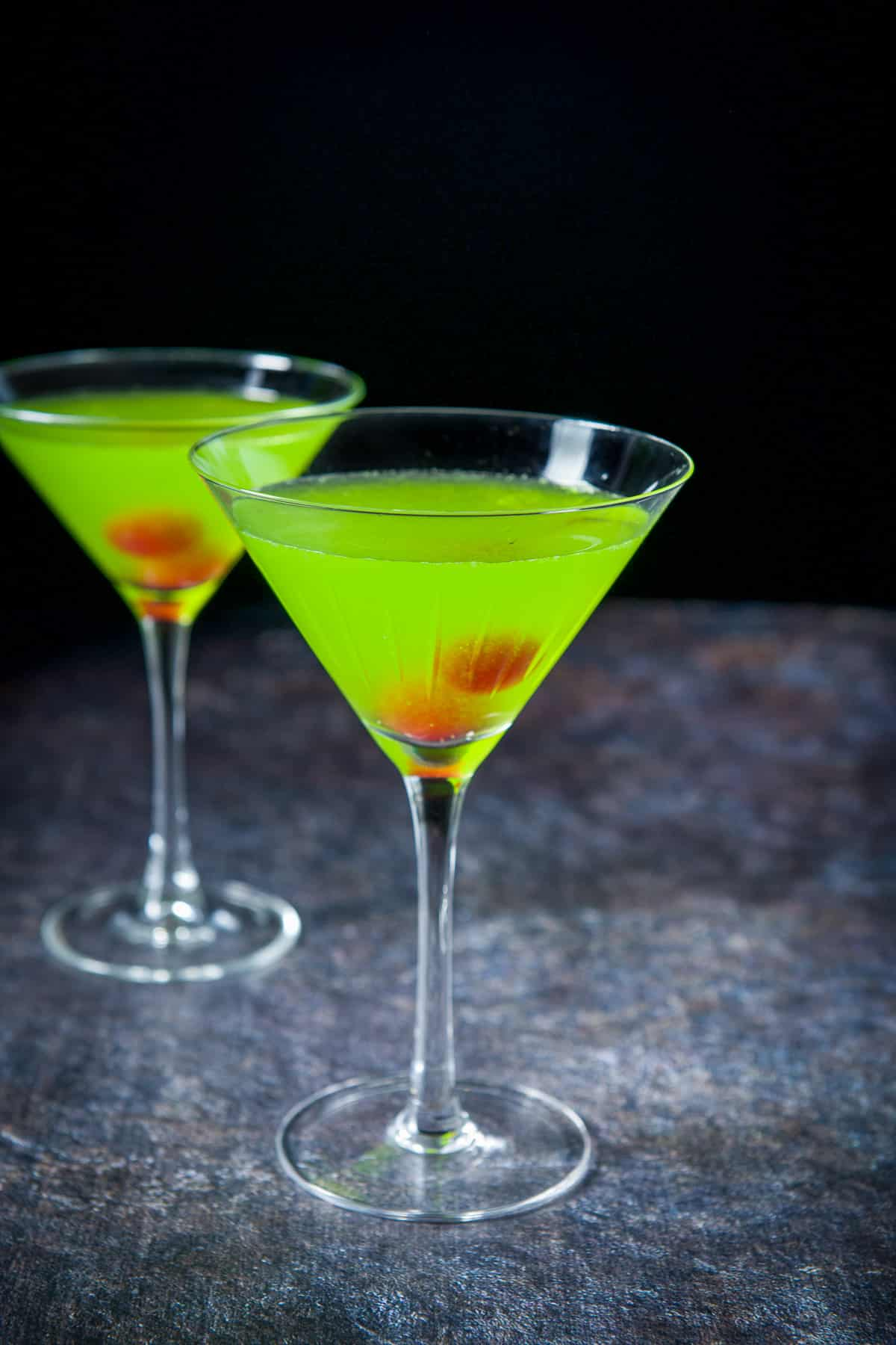 Two martini glasses filled with the green drink with cherries in the glasses as garnish