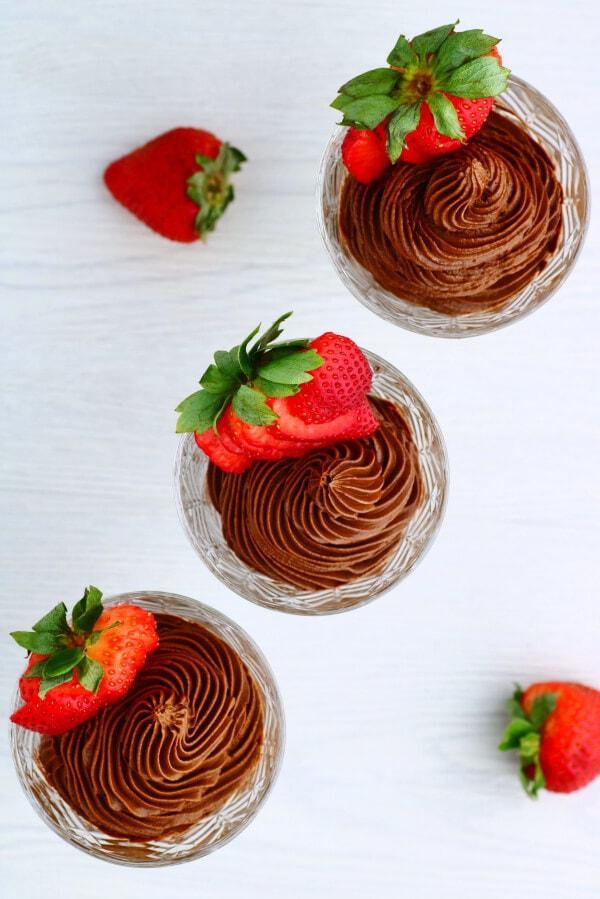 Kristallgläser gefüllt mit dunkler Schokoladen-Avocado-Mousse und einer Erdbeere.