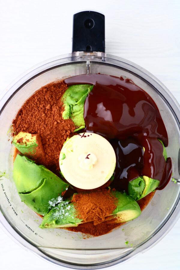 Eine Schüssel mit einer Küchenmaschine, die mit Zutaten gefüllt ist, die für die Herstellung von Schokoladen-Avocado-Mousse benötigt werden.