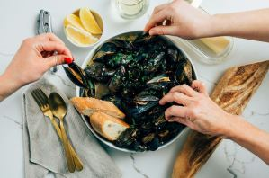 People sharing mussels and white wine sauce