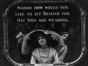 Old photo. Woman wearing large hat and historical dress at the movies.