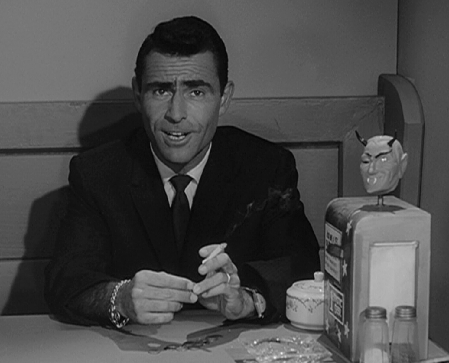Rod Serling at a diner table.