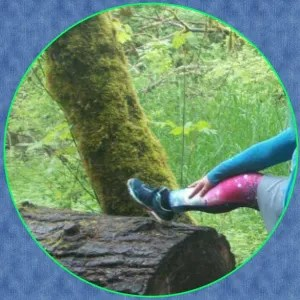 close up of a a woman's leg on a fallen log. She's wearing one of the mocked styles,  colorful leggings as pants