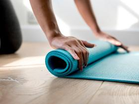 hands rolling up exercise yoga mat