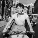 Audrey Hepburn and Gregory Peck smiling on a Vespa in Roman Holiday