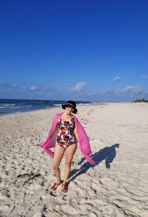 White woman standing on a beach wearing a colorful swimsuit