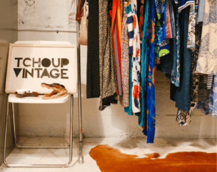 Ladypreneur Lesly Washington. A sign saying Tchoup Vintage beside a colorful rack of clothes