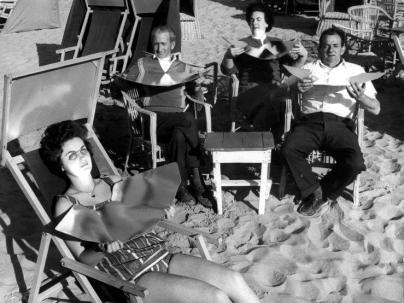 black and white photo of four people on a beach holding foldable tanning reflectors