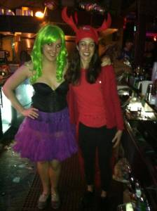 two women in costumes. Elise in a red shirt and crab claw hat. Work uniforms after party