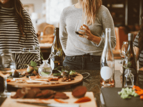 Three women around a table of food drinking wine no visible body anxiety