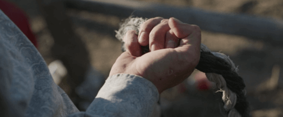 Close up from the rider of a hand holding a rope