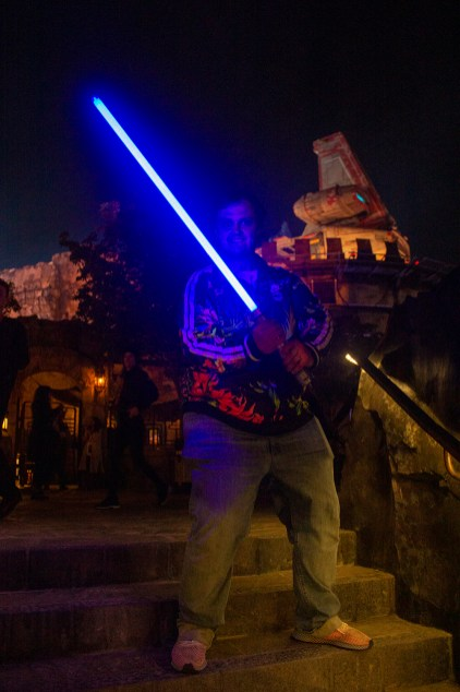A member of the Resistance, actually a guest, wields their custom-built lightsaber at Black Spire Outpost. Photo by Mark Eades.