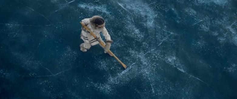 Una mujer con un abrigo blanco encima de un lago congelado de la película The Call of the Wild