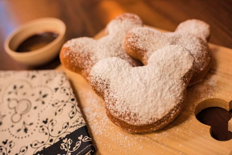 Buñuelos de Mickey Mouse cubiertos de azúcar glass sobre una tabla de madera