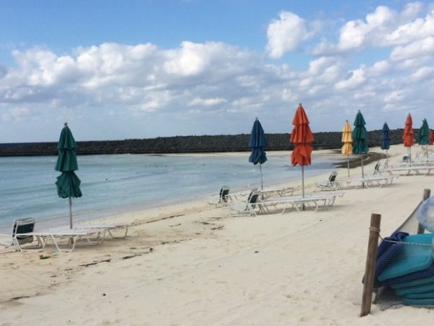 The private beach on Castway Cay. The beach is empty but for a few umbrellas and lounge chairs. The beach os for guests in the private Cabanas.