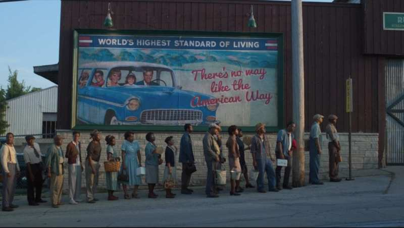 a line of black people queueing for a bus under a car ad for white people