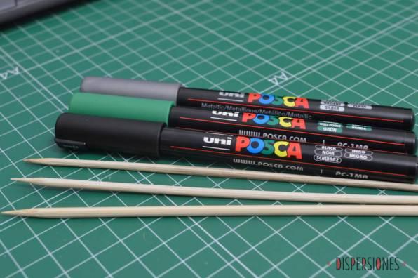 Uni Posca verde, negro y plateado. Brochetas de madera para sujetar las bolas mientras se pintan.