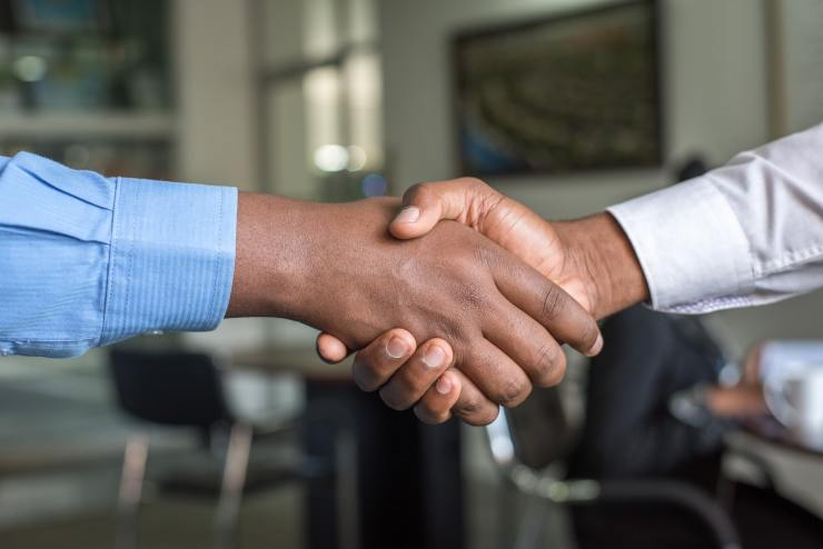 two people with long sleeve polo shirt shaking hands