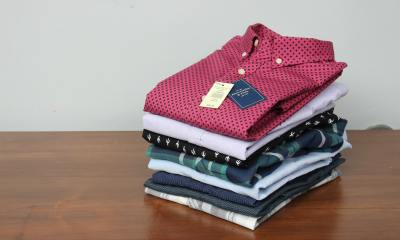 red and white checkered buttoned up shirt piled with other folded shirts