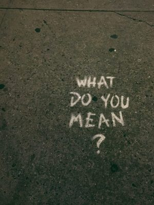 """""""What do you mean?"""" painted on concrete sidewalk"""